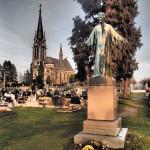 Vítkovský hřbitov, v pozadí kostel Nanebevzetí Panny Marie; k Janovu hrobu dojdete po cestičce vedoucí k bráně, před ní zahnete doprava